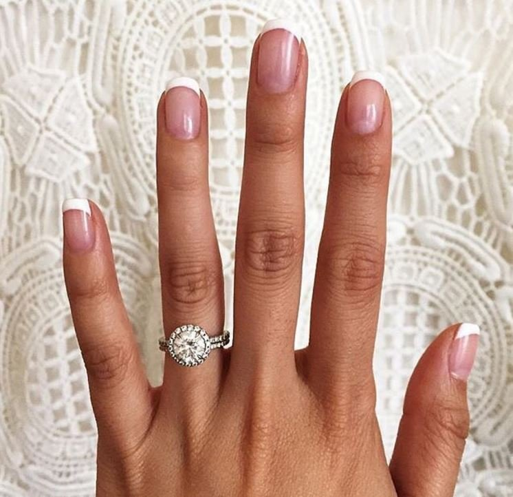 Woman's hand with delicate halo engagement ring