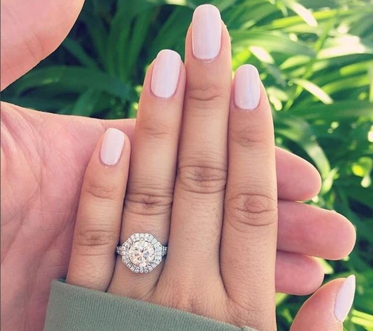 Halo engagement ring on woman's hand