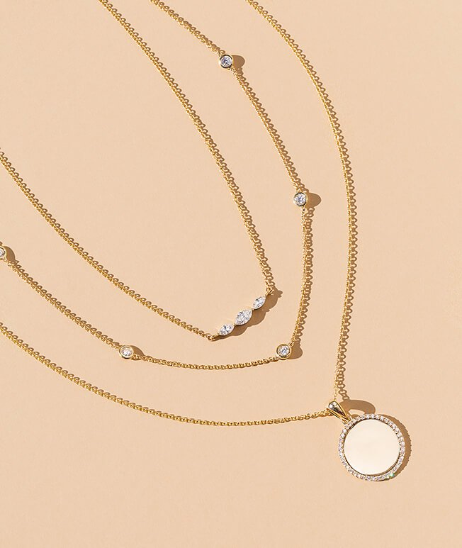 Yellow gold layered necklaces with diamond details