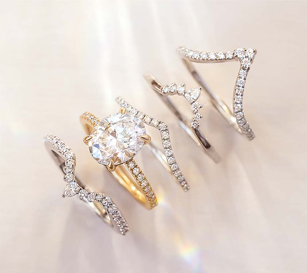 White gold and yellow gold stacked wedding rings with intricate diamond details
