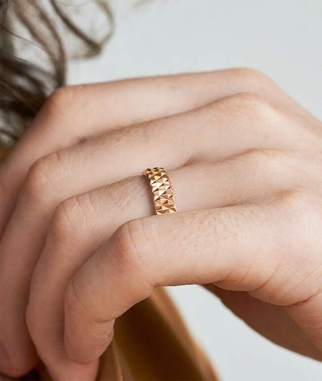 Lustrous rose gold textured ring on hand