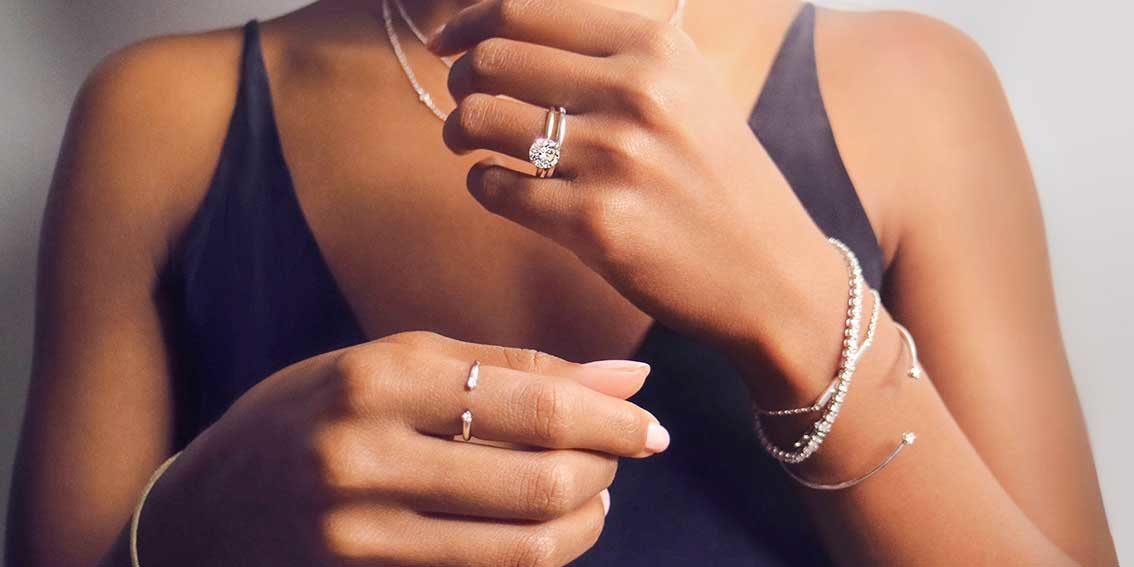 Woman wearing diamond rings, bracelets, and necklaces.