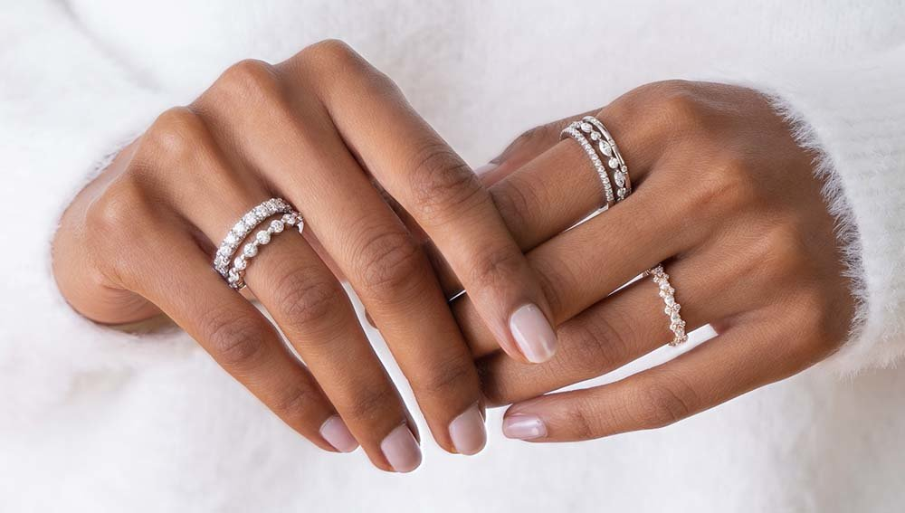 Stacks of diamond eternity rings on hand