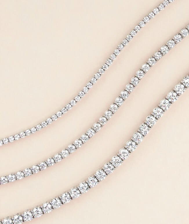 Stack of three lustrous white gold diamond tennis bracelets