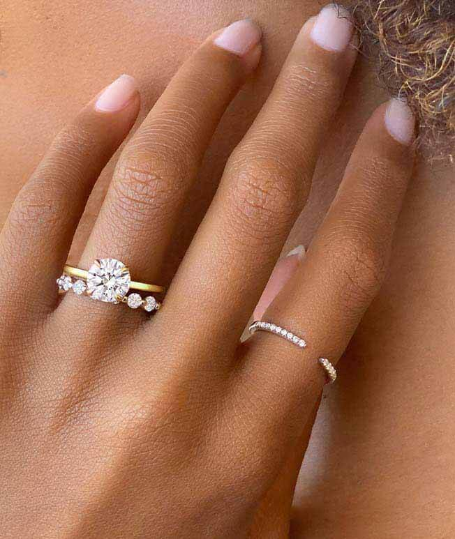 Stack of diamond engagement ring, wedding band, and stacking ring.