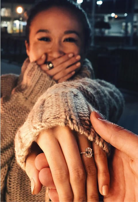 Woman smiling and displaying oval diamond engagement ring